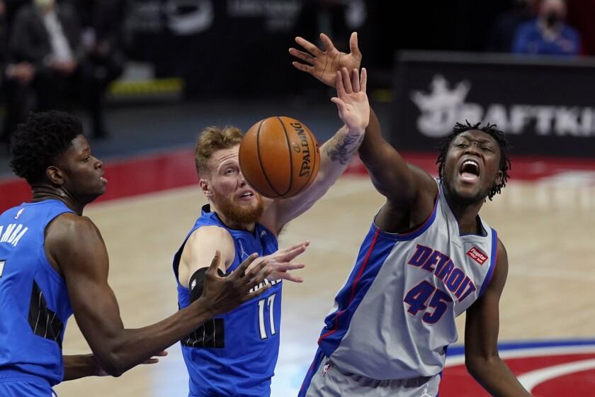 El alero de los Pistons de Detroit Sekou Doumbouya pierde el control del balón frente a James Ennis III y Mo Bamba del Magic de Orlando el lunes 3 de mayo del 2021. (AP Photo/Carlos Osorio)