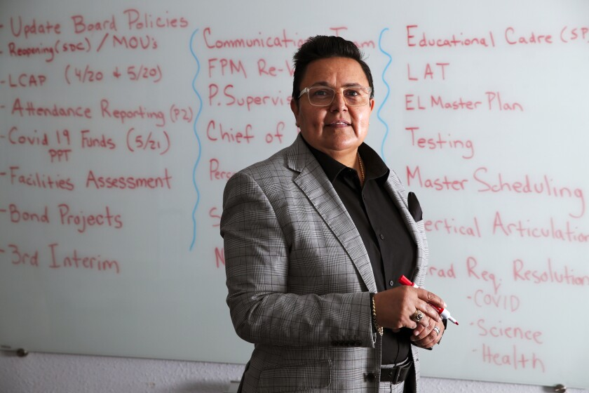 A person stands in front of a whiteboard full of writings.