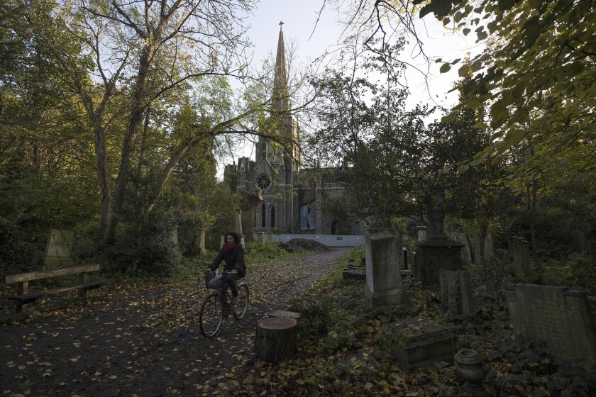 A cyclist rides through Abney Park Cemetery in London.