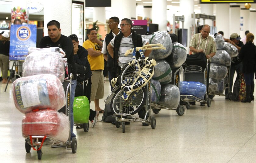 FILE - In this Dec. 19, 2011, file photo, travelers wait in line with their luggage at Miami International Airport before traveling Cuba in Miami. Hundreds of thousands of Cubans and Cuban-Americans fly in and out of Cuba each year thanks to the liberalization of U.S. and Cuban travel rules over the last five years. On Monday, Sept. 1, 2014, the Cuban government will enact new rules meant to take a big bite of that traffic, sharply limiting the amount of goods people can bring into Cuba in their luggage, and ship by boat from abroad. (AP Photo/Lynne Sladky, File)