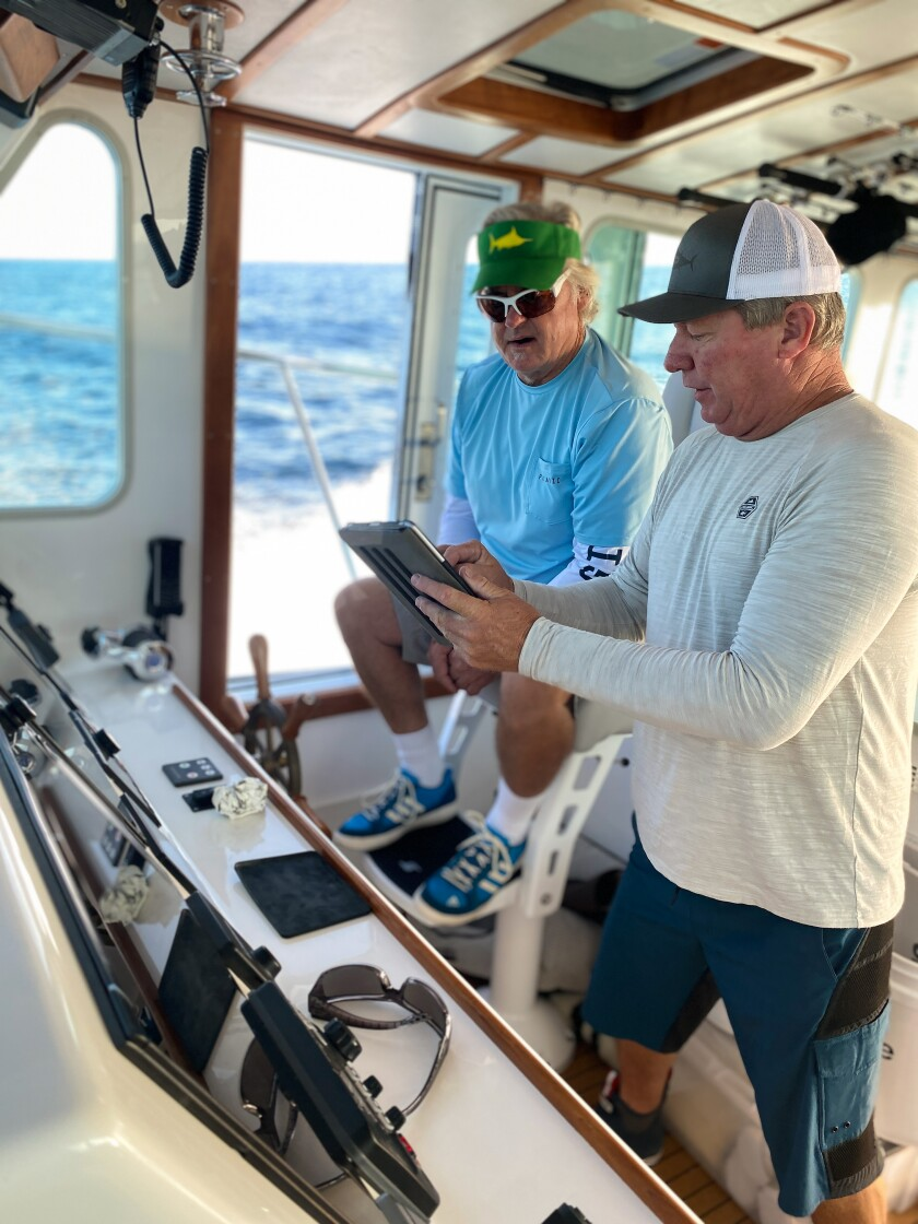 RV Pilar captain Jake Russell (left) and second captain Bob Woodard work to remove plastics from local waters.