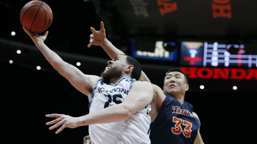 UC Irvine guard Spencer Rivers, left, lays up a shot against Cal State Fullerton forward Johnny Wang