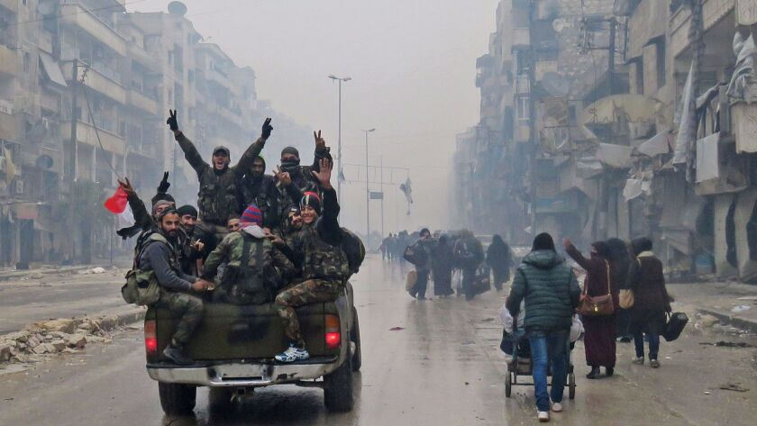 Pro-government fighters drive past residents fleeing violence in Aleppo, Syria, on Dec. 13.