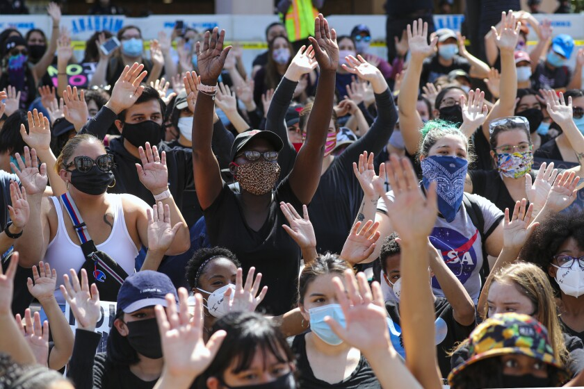 Protesters raise their hands in a rally on the steps of Anaheim City Hall on June 3.