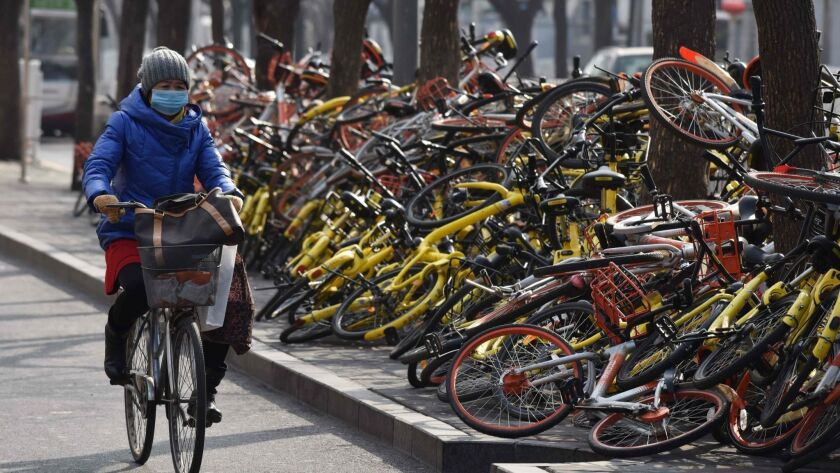 A woman rides past shared bicycles piled beside a road in Beijing in February 2018. China issued national guidelines governing bike-sharing operations in an effort to address complaints over an accumulation of millions of bikes on city streets.