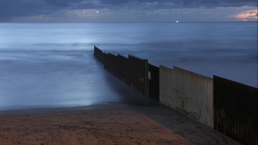 In this Feb. 28, 2018 photo, the sun sets over the U.S.-Mexico border wall that runs into the Pacifi