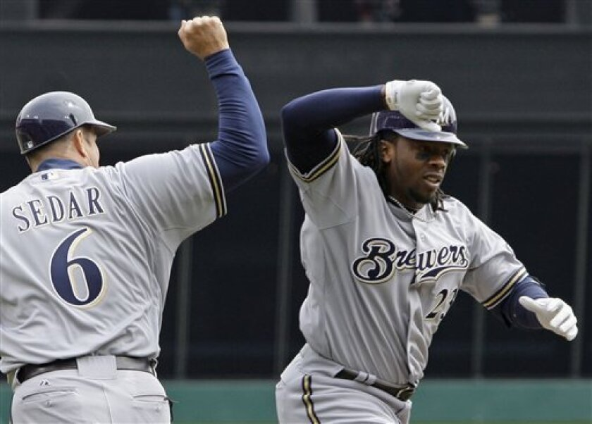 Milwaukee Brewers second baseman Rickie Weeks (23) is congratulated by third base coach Ed Sedar (6) after Weeks hit a solo home run off Cincinnati Reds starting pitcher Edinson Volquez in the first inning of a major league baseball game, Thursday, March 31, 2011 in Cincinnati. (AP Photo/Al Behrman