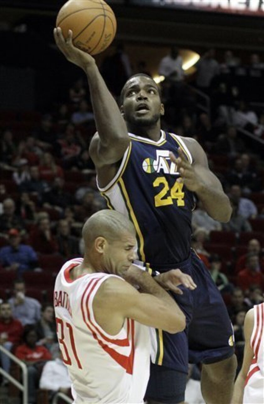 Utah Jazz forward Paul Millsap (24) tries to shoot over Houston Rockets' Shane Battier (31)during the first half of an NBA basketball game, Saturday, Jan. 8, 2011, in Houston. Millsap was charged for an offensive foul on the play. (AP Photo/Pat Sullivan)