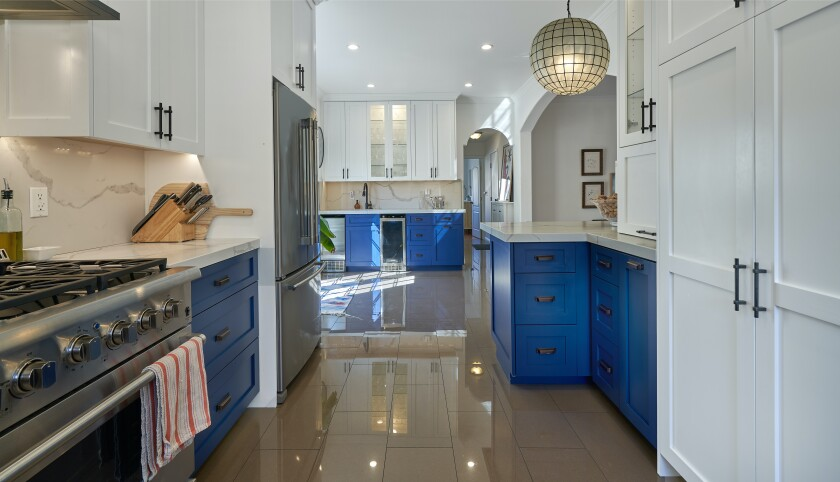 The remodeled kitchen with blue and white cabinetry.