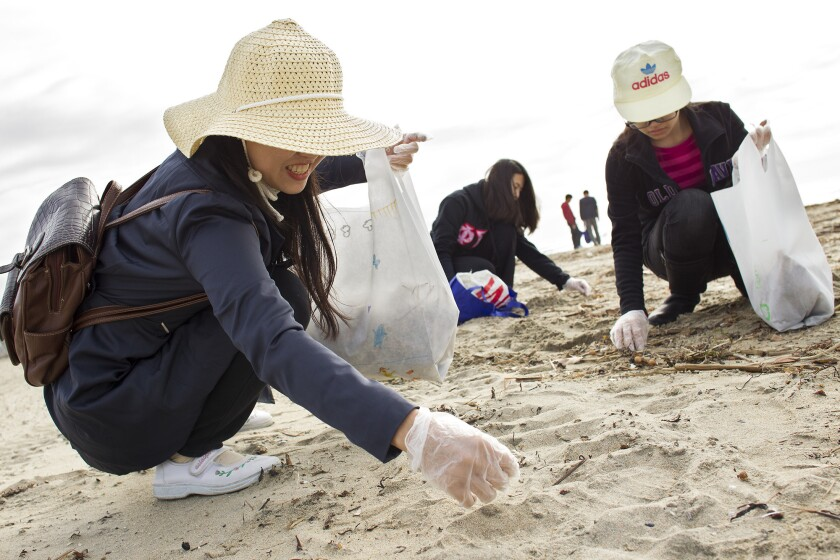 Volunteers pick up plastic during Orange County Coastkeepers' monthly cleanup at Huntington State Beach.