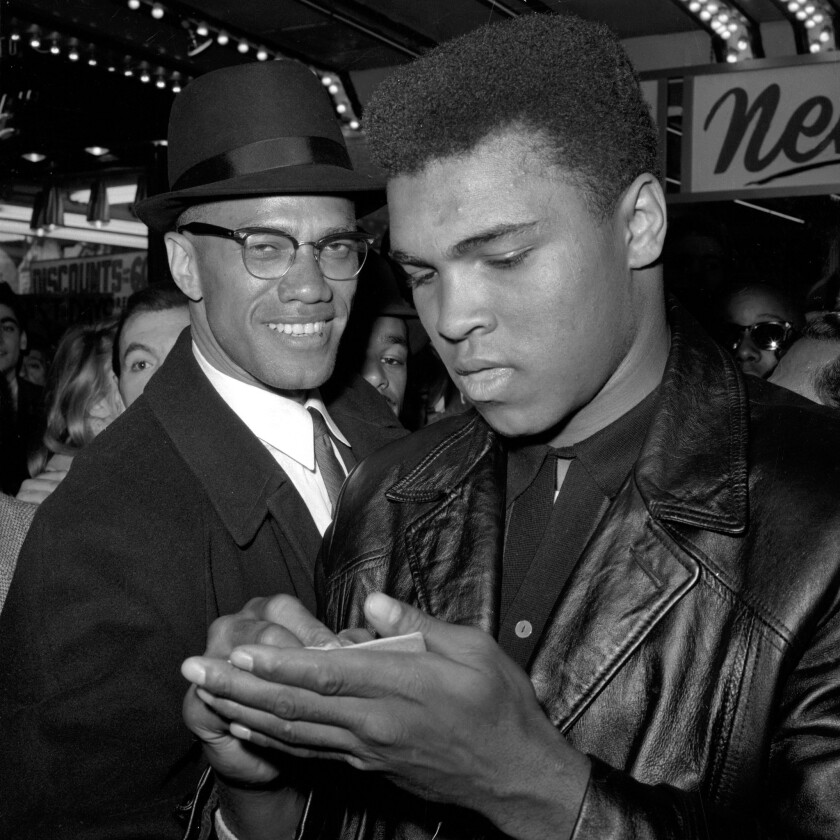 In this March 1, 1964 file photo, Muhammad Ali, right, stands with Malcolm X outside the Trans-Lux Newsreel Theater on Broadway at 49th Street in New York.