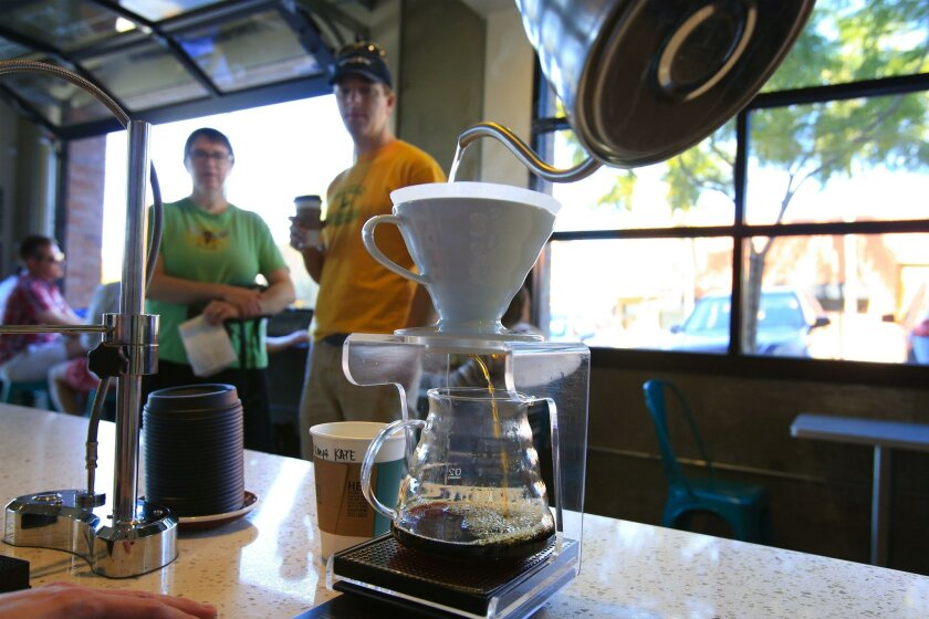 Customer Kae Beneixen waits for a V60 cup of coffee as Joseph Esparza a barista at Bird Rock Coffee Roasters pour hot water over fresh coffee grind for the V60 pour over. Waiting with Beneixen is Chris Hedge. The Geisha coffee is currently sold out, but when it is in stock, this is one of the ways