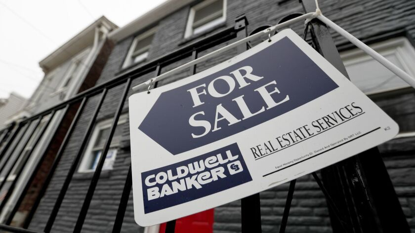FILE- In this Jan. 4, 2019, file photo a sign hangs outside a house for sale in Pittsburgh's Lawrenc