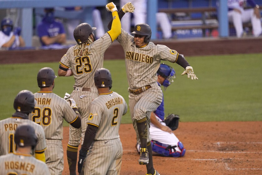 San Diego Padres' Manny Machado, second from right, celebrates with Fernando Tatis Jr., center, after hitting a grand slam as Los Angeles Dodgers catcher Austin Barnes, right, kneels at the plate during the third inning of a baseball game Tuesday, Aug. 11, 2020, in Los Angeles. (AP Photo/Mark J. Terrill)