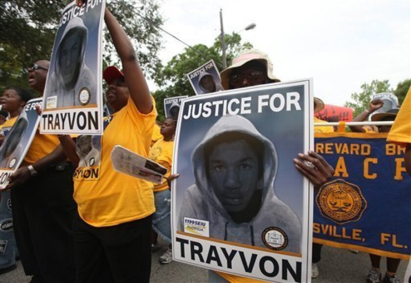 """Protestors hold up signs in a march and rally for slain Florida teenager Trayvon Martin on Saturday, March 31, 2012 in Sanford, Fla.  Protesters carried signs, chanted """"Justice for Trayvon,"""" and clutched the hands of their children while they walked from Crooms Academy of Information Technology, th"""
