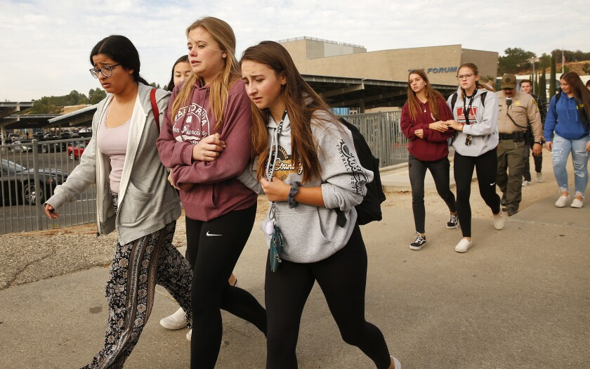 Police officers escort students away from Saugus High School after a gunman opened fire on the Santa Clarita campus early Thursday.