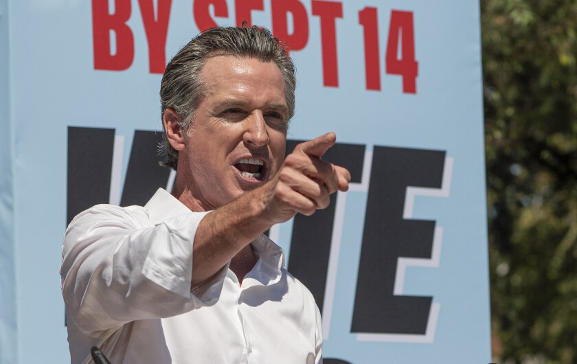 """California Gov. Gavin Newsom stands in front of a sign reading """"By Sept. 14: Vote."""""""