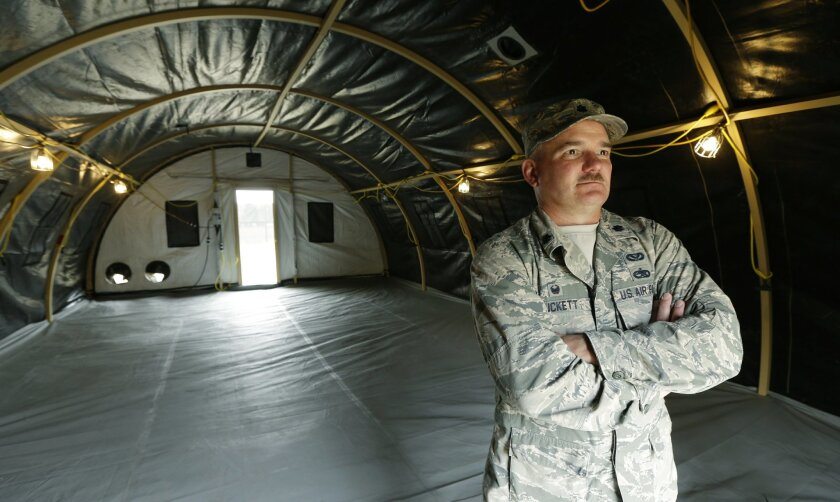 In this photo taken May 24, 2016, Washington Air National Guard Lt. Col. Curt Puckett, commander of the Guard's 141st Civil Engineer Squadron based at Fairchild Air Force Base in Spokane, Wash., stands in a temporary living structure his soldiers helped assemble at Joint Base Lewis-McChord in Washi