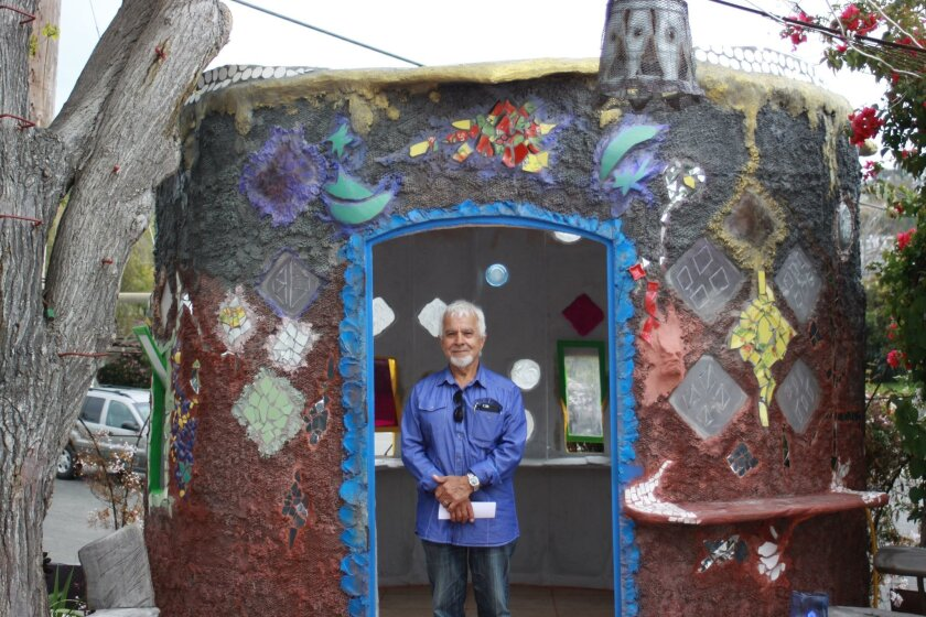 La Jolla artist Nasser Pirasteh with his sculpture, which the city claims is an 'accessory structure' on his property and visible from Nautilus Street.