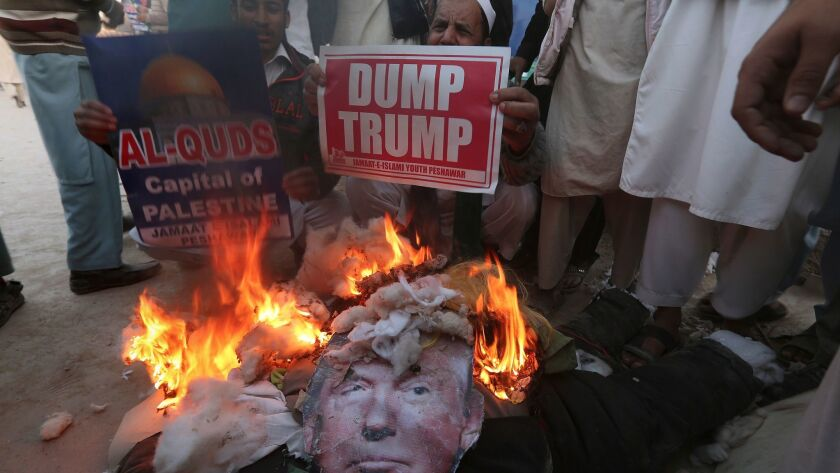 Supporters of Jamaat-e-Islami burn an effigy of U.S. President Donald Trump at an anti-American rall