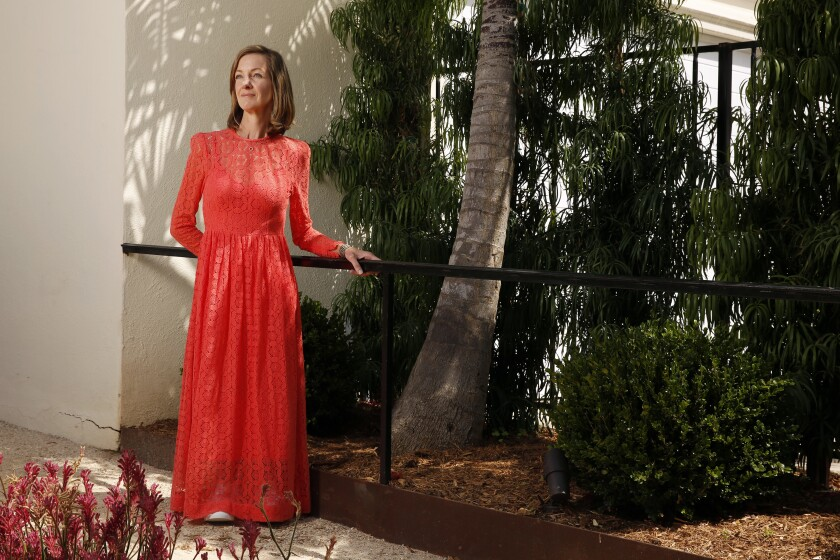 A woman in a long red dress stands holding a railing on a path under a tree