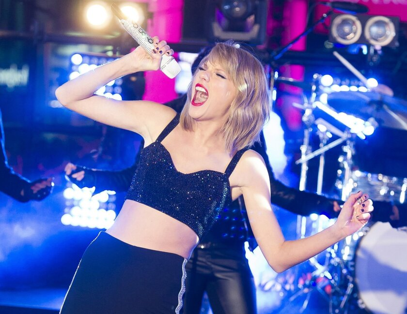 FILE - In this Dec. 31, 2014 file photo, Taylor Swift performs in Times Square during New Year's Eve celebrations in New York. Swift, along with Amanda Lambert, Kenny Chesney, George Strait, Garth Brooks,  Reba McEntire and Brooks & Dunn will receive a special honor at the Academy of Country Music'