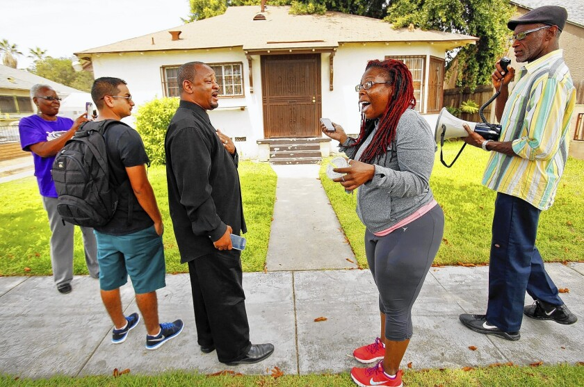Community activist Najee Ali, center left, exchanges words with Jasmyne Cannick, center right, outside the home of Compton school board member Skyy Fisher following his arrest. Cannick is a spokeswoman for Fisher, while Ali wants him to resign.