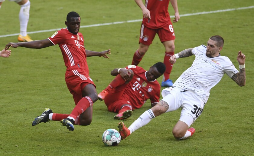Bayern's Tanguy Nianzou, left, and Union's Robert Andrich challenge for the ball during the German Bundesliga soccer match between Bayern Munich and FC Union Berlin at Allianz Arena in Munich, Germany, Saturday, April 10, 2021.(Andreas Gebert/Pool via AP)