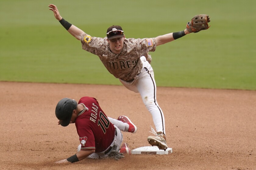 Padres second baseman Jake Cronenworth, top, leaps over Arizona Diamondbacks' Josh Rojas during June 27 game.