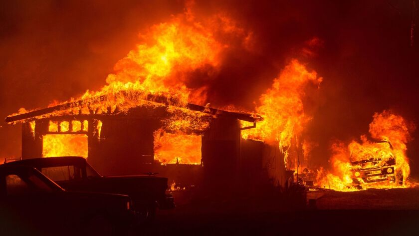 A car and house near Oroville, Calif., are engulfed in flames by the Wall fire on Saturday.