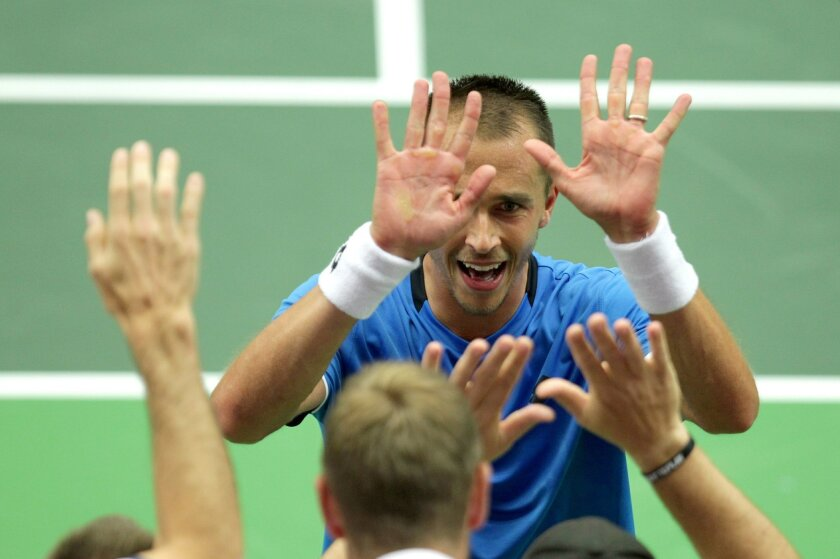 Lukas Rosol of Czech Republic celebrates with teammates after beating Jo-Wilfried Tsonga of France during the tennis Davis Cup quarterfinal match in Trinec, Czech Republic, Friday, July 15, 2016. Rosol won 6-4, 3-6, 4-6, 7-6, 6-4. (Petr Sznapka/CTK via AP) SLOVAKIA OUT