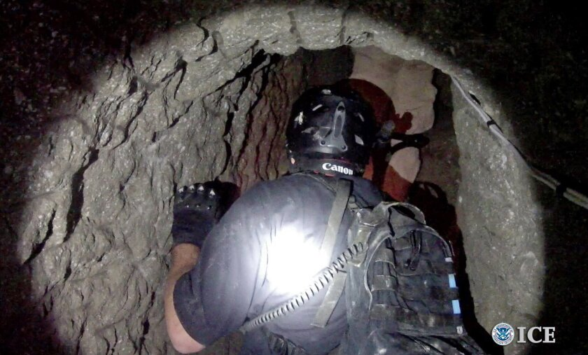 An Oct. 31, 2013, photo released by U.S. Immigration and Customs Enforcement shows agents in a tunnel designed to smuggle drugs from Tijuana, Mexico, to San Diego. The tunnel is equipped with electricity, ventilation and a rail system, U.S. authorities said.  Authorities seized more than 8 tons of
