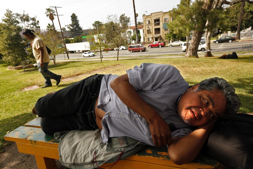 "Timoteo Arevalos, 55, rests in Hollenbeck Park in Boyle Heights, June 6. Arevalos, who has been homeless for a few months, spends his days in the park. ""I feel safe. This is home,"" he said."