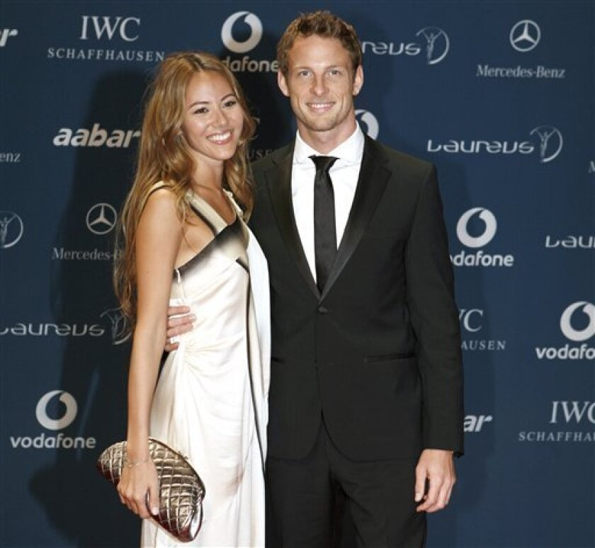 British F1 driver Jenson Button with his companion arrives for the Laureus Awards in Abu Dhabi, United Arab Emirates, Wednesday March 10, 2010. (AP Photo/Farhad Berahman)