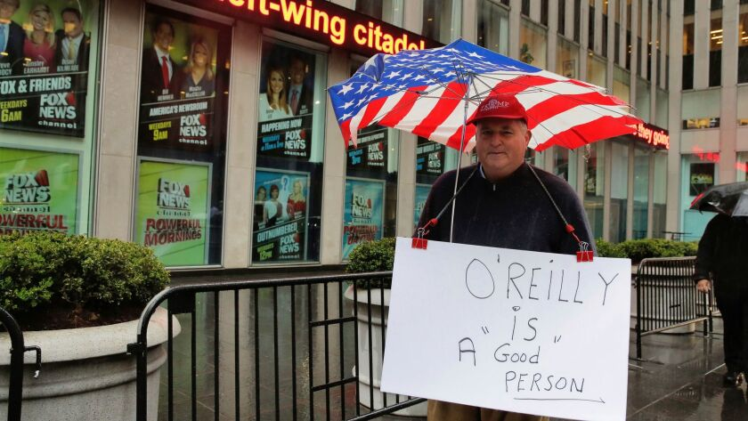 Douglas Esposit of New York hoists a Bill O'Reilly sign as he walks by the 21st Century Fox headquarters Thursday in New York.