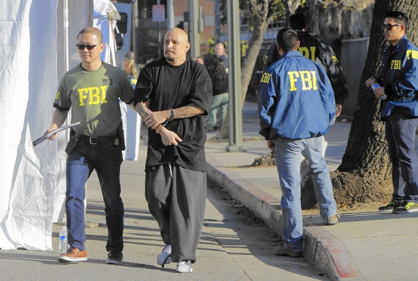 A suspect is processed in downtown Los Angeles after at least 38 members of the Big Hazard gang were indicted under federal anti-racketeering statutes.