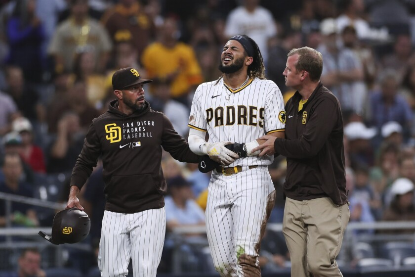The Padres' Fernando Tatis Jr., middle, is helped off the field by manager Jayce Tingler, left, and a trainer July 30, 2021.