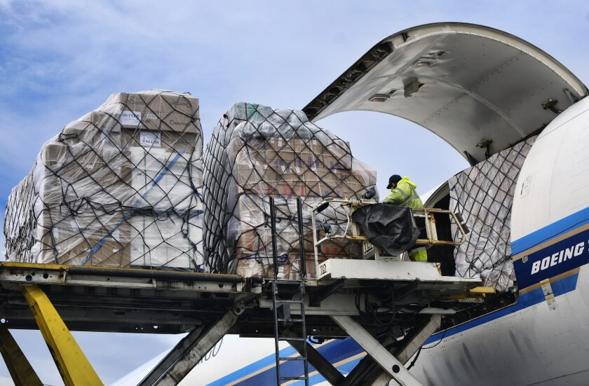 Crews at Los Angeles International Airport unload pallets of supplies of medical personal protective equipment on Friday.