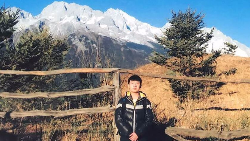 An undated picture released by his family shows Yu Huan at an unknown location. He attacked the thugs who tormented his mother, killing one of them.