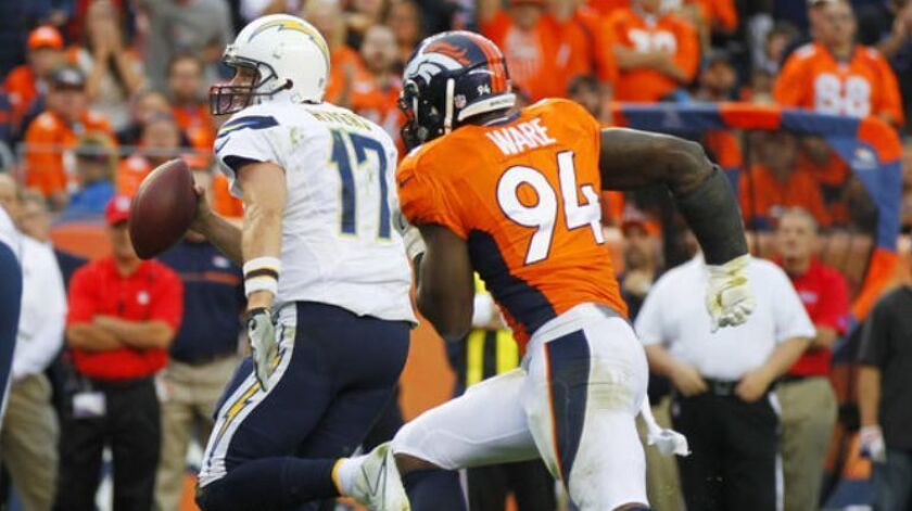 Chargers' Philip Rivers is chased by Broncos' DeMarcus Ware in the 4th quarter in Denver.