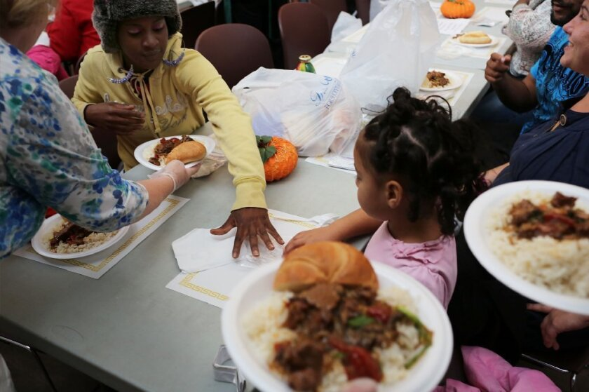 People eat dinner at the Cathedral Kitchen soup kitchen which serves 300 to 600 meals a day, six days a week, to the needy and hungry in Camden, New Jersey. Poor people may think differently about their resources than the rich, a new study finds.