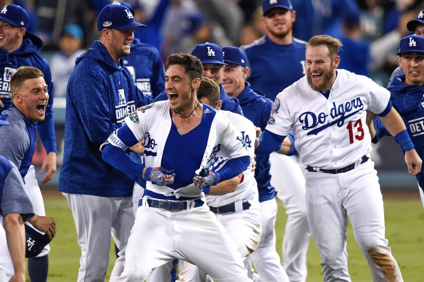 Cody Bellinger #35 of the Los Angeles Dodgers celebrates with teammates after hitting a walk-off single in the thirteenth inning against the Milwaukee Brewers to win Game Four of the National League Championship Series 2-1 at Dodger Stadium on October 16, 2018 in Los Angeles, California.