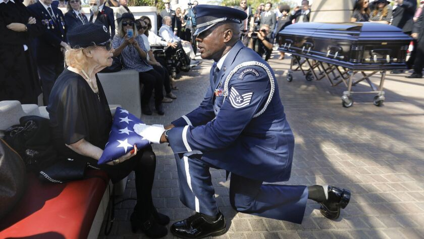Winifride Rowe, left, the wife of retired Air Force Captain Claude A. Rowe, Jr., is presented the American flag that draped her husband's casket, by a member of the March Air Force Base Honor Guard.