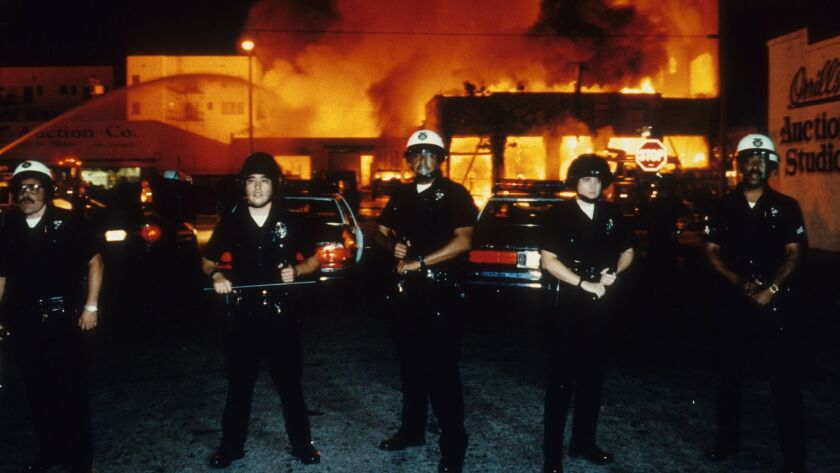 LAPD officers stand guard as fire units battle a blaze near 19th Street and Adams Boulevard on April 30, 1992.