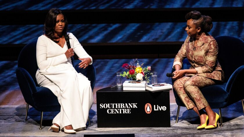Former First Lady Michelle Obama, left, speaks with Nigerian author Chimamanda Ngozi Adichie at the Royal Festival Hall in London on Dec. 03.