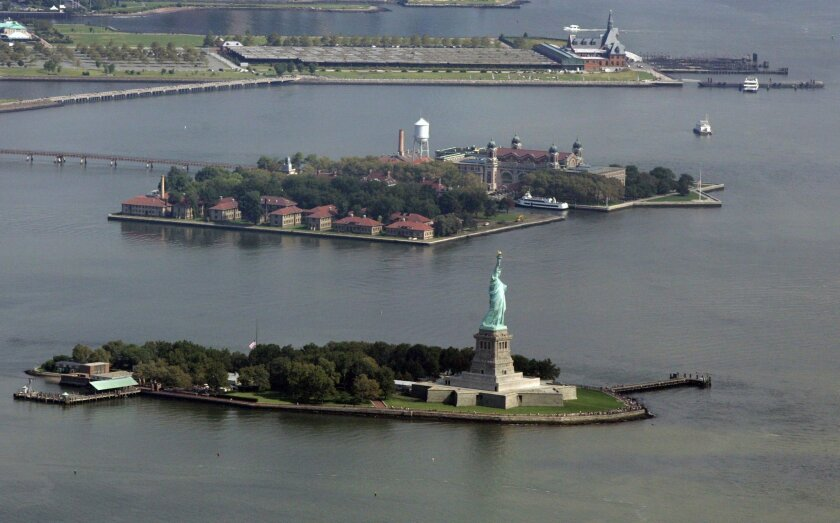 FILE - In this Thursday, Sept. 11, 2008, file photo, the Statue of Liberty on Liberty Island, bottom, is seen near Ellis island, middle, and the historic Central Railroad of New Jersey Terminal, top, in Jersey City, N.J. A low-rise hotel or an amusement park could be coming to Liberty State Park if some of the developments outlined Tuesday, Nov. 24, 2915, in a report from Gov. Chris Christie's administration come to fruition. (AP Photo/Mel Evans, File)