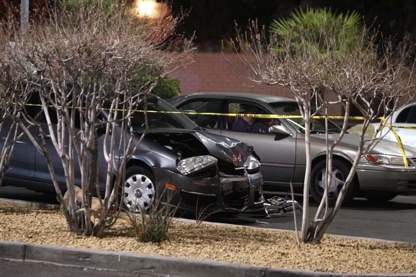 FILE - In this Jan. 21, 2014 file photo, a damaged car is seen at the scene of a fatal road rage incident near the corner of Tropicana Avenue and Rainbow Boulevard in Las Vegas. Authorities say a man shot a motorist to death in a vehicle with two children in the backseat in an apparent road-rage co