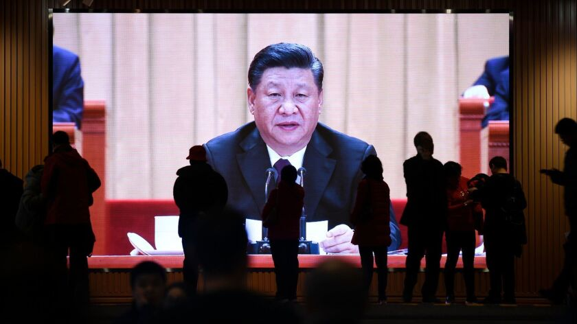 People walk past a screen showing video footage of Chinese President Xi Jinping at an exhibition at the National Museum of China in Beijing on Feb. 27.