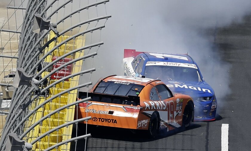Daniel Suarez (19) spins in front of Elliott Sadler as they exit Turn 4 during the NASCAR Xfinity Series auto race at the Charlotte Motor Speedway in Concord, N.C., Saturday, May 28, 2016. (AP Photo/Gerry Broome)