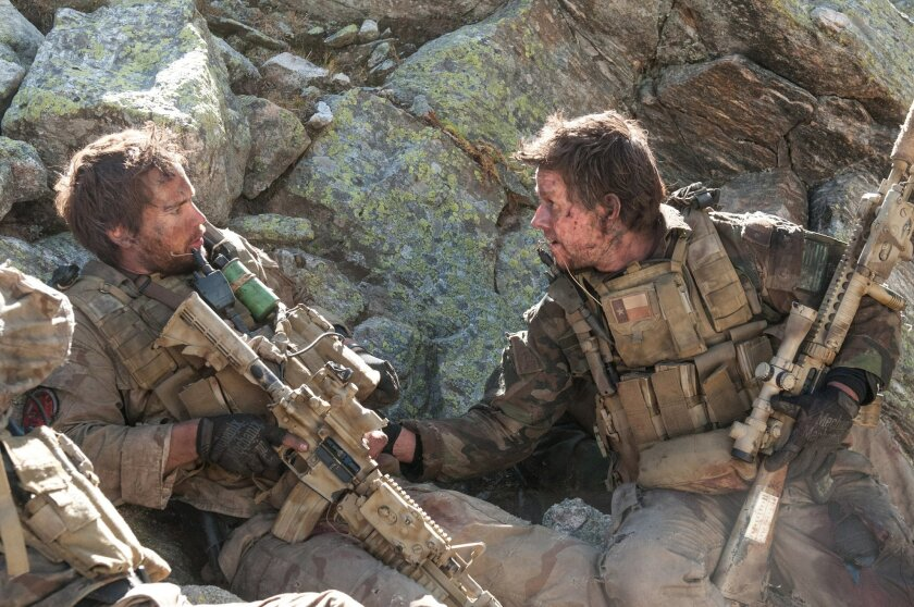 """Michael Murphy (TAYLOR KITSCH), left, and Marcus Luttrell (MARK WAHLBERG) in """"Lone Survivor"""", the incredible story of four Navy SEALs on a covert mission to neutralize a high-level Taliban operative who are ambushed by enemy forces in the mountains of Afghanistan. The film is based on The New York"""